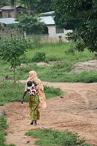 Photo showing a woman in a forested landscape in Africa, carrying a baby on her back. Photo: Nelson Grima, IUFRO.