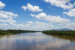 Photo showing a river, with clouds in the sky and trees at the banks. Photo by Jose Eduardo Camargo on Pixabay