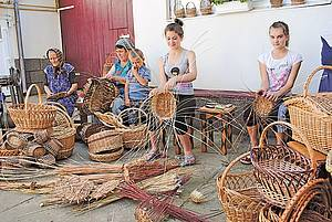 Photo showing women producing baskets and other wicker products.