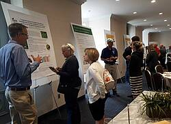 Photo showing IUFRO Christmas Tree Working Party members confer around research posters. Photo provided by Christmas Tree Working Party.